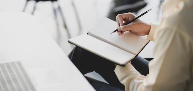 Jonge zakenman werkt aan zijn project tijdens het schrijven op laptop