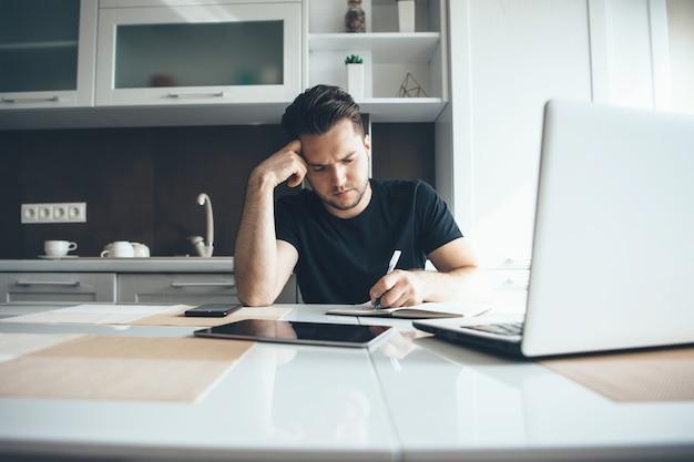Jonge zakenman werkt op afstand vanuit huis in de keuken met behulp van een laptop terwijl hij iets schrijft