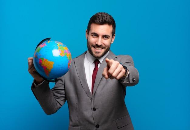 Jonge zakenman wijzend op de camera met een tevreden, zelfverzekerde, vriendelijke glimlach, die ervoor kiest dat u een wereldbolkaart vasthoudt