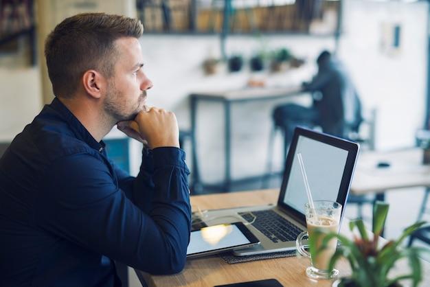 Jonge zakenman zit in café-bar met laptop wordt bezorgd en na te denken over een oplossing voor zijn probleem