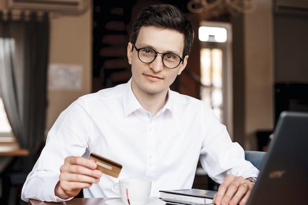 Jonge zakenman zit in een coffeeshop met een creditcard in de hand en kijkt naar de camera