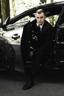 Jonge zakenman zit in een dure auto en kijkt naar de camera. de bruidegom rijdt. zakenman. succesvolle man. rijke man.