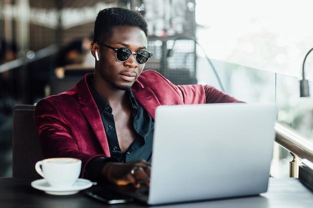 Jonge zakenman zit naast laptop en kijkt naar iets.