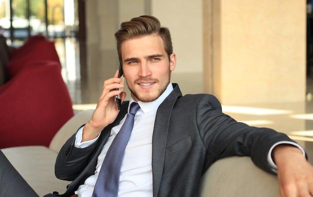 Jonge zakenman zit ontspannen op de bank in de lobby van het hotel te telefoneren, wachtend op iemand.