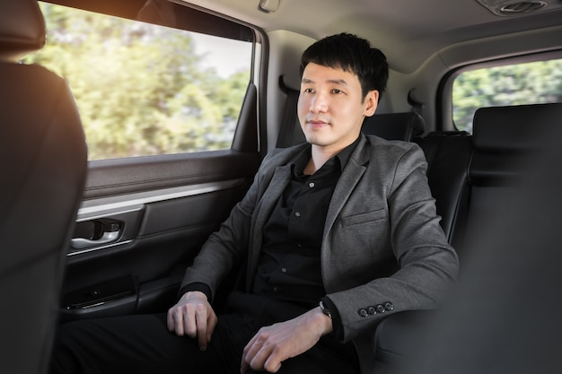 Jonge zakenman zit op de achterbank van de auto