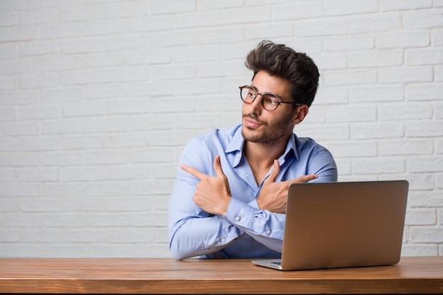 Jonge zakenman zitten en werken aan een laptop verward en twijfelachtig