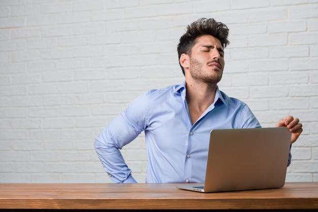 Jonge zakenman zitten en werken op een laptop met pijn in de rug als gevolg van werkstress