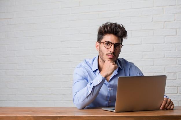 Jonge zakenman zitten en werken op een laptop te denken en te kijken, verward over een idee, zou proberen om een oplossing te vinden