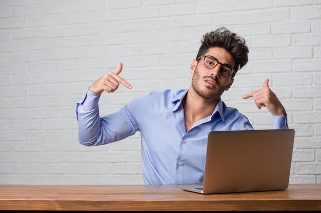 Jonge zakenman zitten en werken op een laptop trots en zelfverzekerd