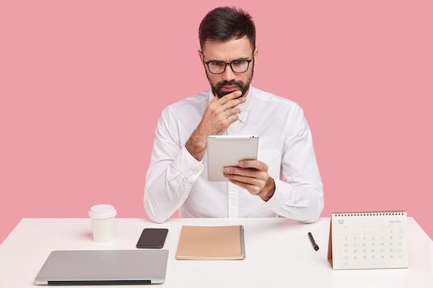 Jonge zakenman zittend aan een bureau met gadgets