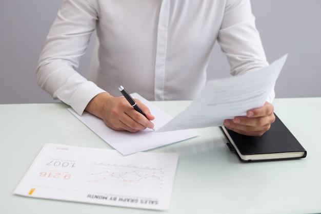 Jonge zakenman zittend aan tafel en werken met papieren