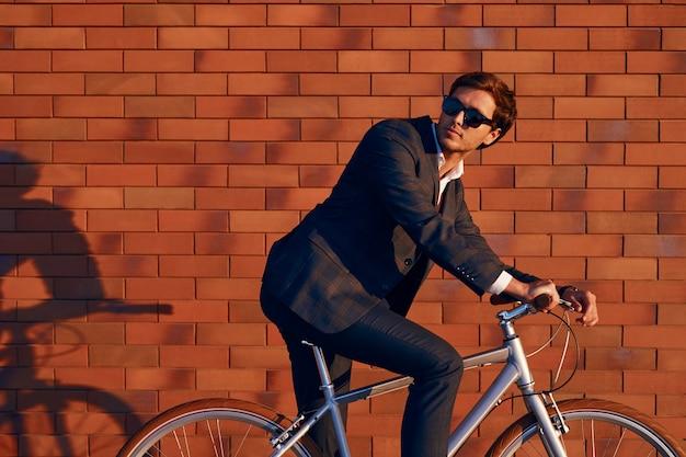 Jonge zakenman zittend op de fiets tegen bakstenen muur