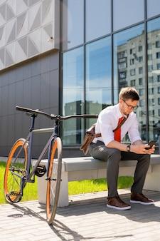 Jonge zakenman zittend op een bankje op zonnige zomerdag en scrollen in smartphone terwijl het hebben van pauze buitenshuis door zakencentrum