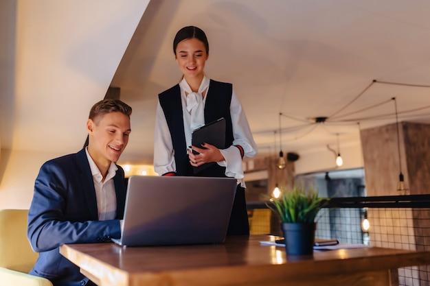 Jonge zakenmannen jongen en meisje werken met een laptop, een tablet en notities in het café