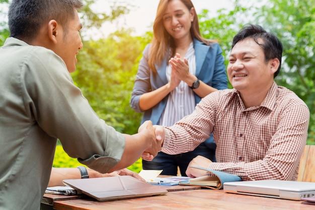Jonge zakenmannen onderhandelen met klanten. en schud de hand na de onderhandelingen.
