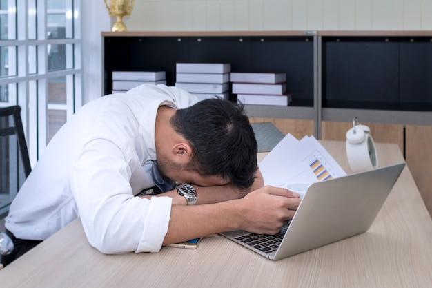 Jonge zakenmanslaap en overwerkt dichtbij laptop op kantoor.