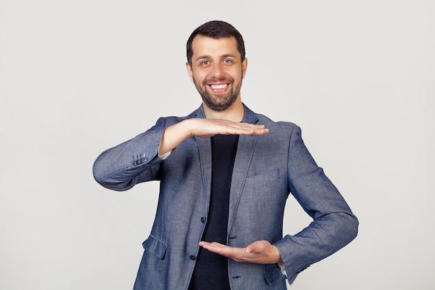 Jonge zakenmens met een baard in een jasje, gebarend met zijn handen die een groot en groot formaatteken een symbool van maat tonen.