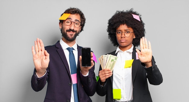Jonge zakenmensen die er serieus, streng, ontevreden en boos uitzien met een open palm die een stopgebaar maakt. humoristisch bedrijfsconcept