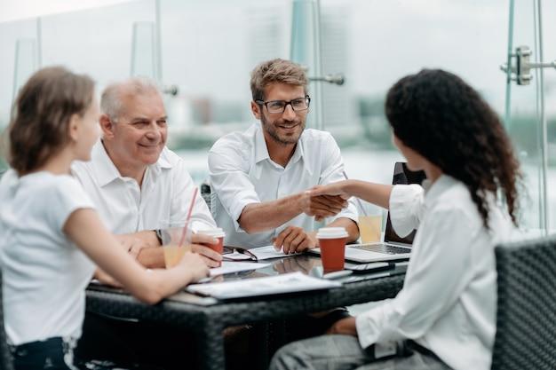 Jonge zakenmensen die handen schudden tijdens een bijeenkomst in een zakencentrum