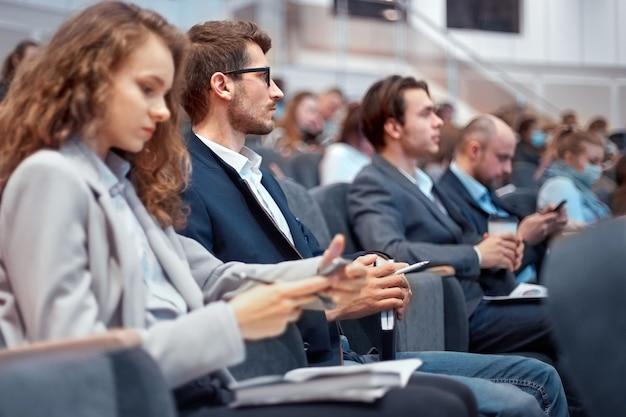 Jonge zakenmensen die hun smartphones gebruiken tijdens de workshop