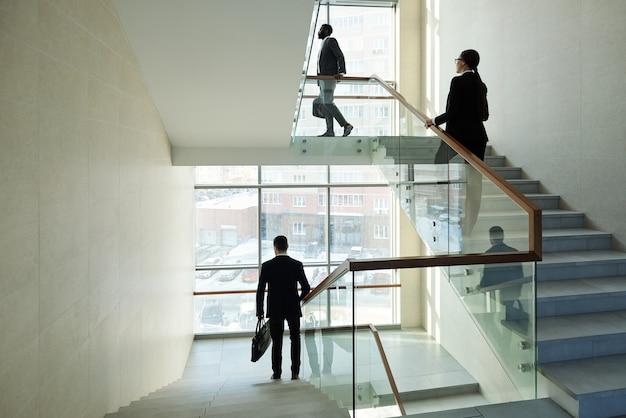 Jonge zakenmensen die naar boven lopen voor werk en een elegante officemanager die naar beneden gaat terwijl ze naar huis gaan