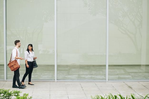 Jonge zakenmensen die over straat lopen en nieuwe projecten en ideeën bespreken