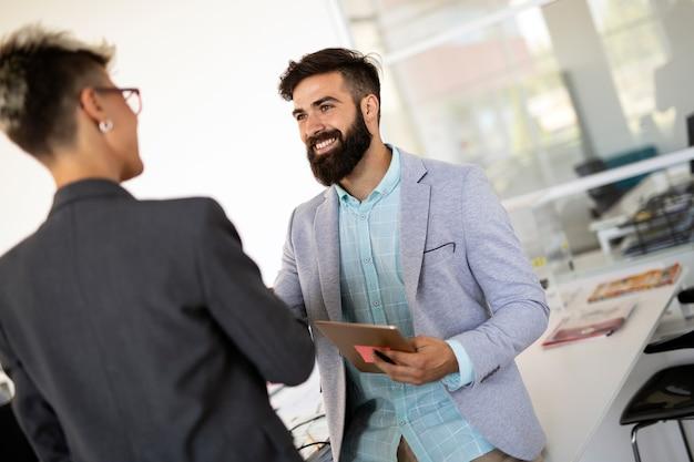 Jonge zakenmensen die plezier hebben en chatten op het kantoor op de werkplek
