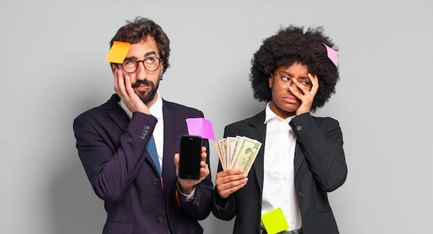 Jonge zakenmensen die zich vervelen, gefrustreerd en slaperig voelen na een vermoeiende, saaie en vervelende taak, waarbij ze hun gezicht met de hand vasthouden. humoristisch bedrijfsconcept