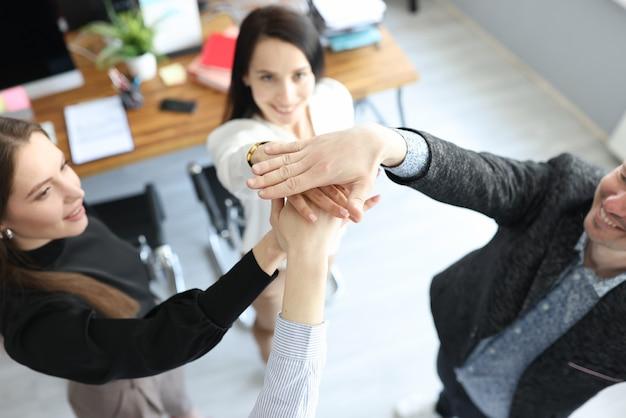 Jonge zakenmensen hand in hand samen en tonen steun en eenheidsclose-up