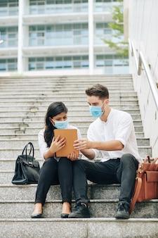 Jonge zakenmensen in medische maskers zittend op stappen en kijken naar video op digitale tablet