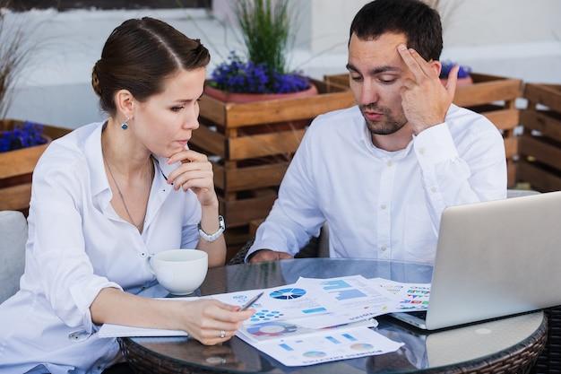 Jonge zakenmensen moe werken achter computer aan balie in café