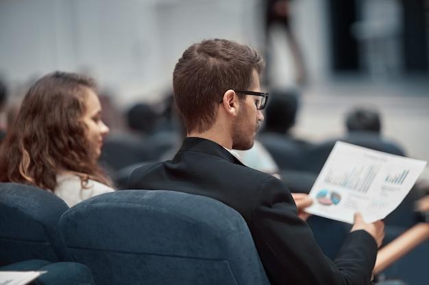 Jonge zakenmensen zitten in de conferentiezaal