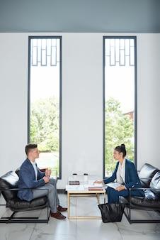 Jonge zakenpartners die in de lounge van het kantoorgebouw bijeenkomen en financiële verslagen en contactgegevens bespreken