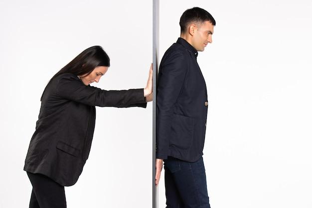 Jonge zakenpartners, gescheiden door een muur, duwt de zakenvrouw de man achter de muur