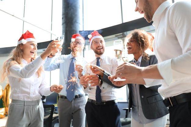 Jonge zakenpartners steken bengaalse lampen aan en drinken champagne in een modern kantoor. vrolijk kerstfeest en een gelukkig nieuwjaar.