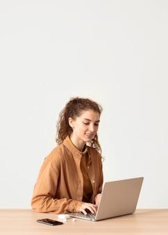 Jonge zakenvrouw binnenshuis werken vanaf laptop