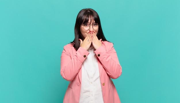 Jonge zakenvrouw blij en opgewonden, verrast en verbaasd over de mond met handen, giechelend met een schattige uitdrukking