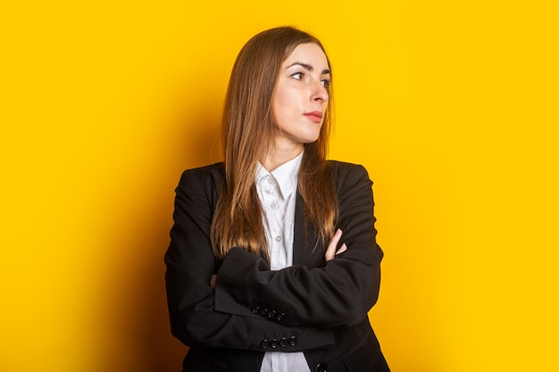 Jonge zakenvrouw dame in een zwart jasje kijkt naar de zijkant op een geel.