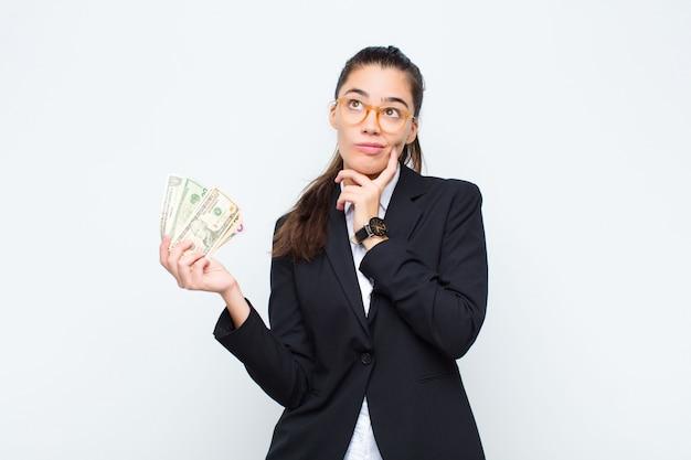 Jonge zakenvrouw denken, twijfelachtig en verward voelen, met verschillende opties, zich afvragend welke beslissing te nemen met bankbiljetten met rekeningen