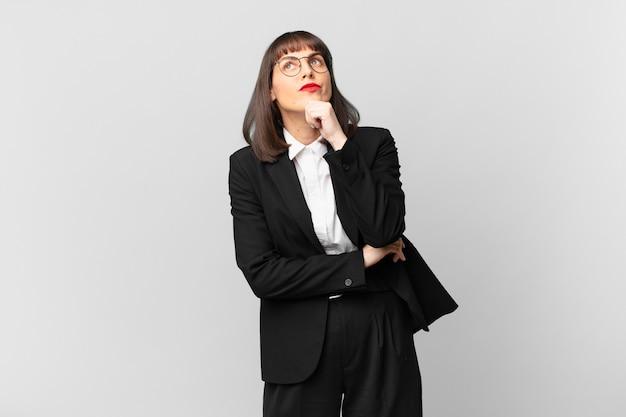 Jonge zakenvrouw denkt, voelt zich twijfelachtig en verward, met verschillende opties, zich afvragend welke beslissing ze moet nemen