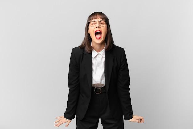 Jonge zakenvrouw die agressief schreeuwt, erg boos, gefrustreerd, verontwaardigd of geïrriteerd kijkt, nee schreeuwt