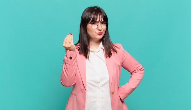 Jonge zakenvrouw die capice of geldgebaar maakt en u vertelt uw schulden te betalen!