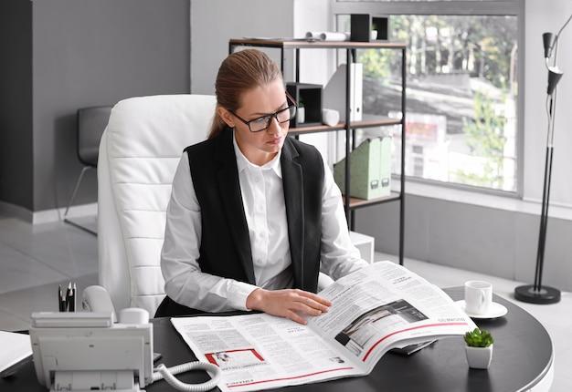 Jonge zakenvrouw die de krant leest op kantoor