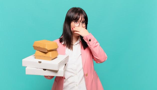 Jonge zakenvrouw die de mond bedekt met handen met een geschokte, verbaasde uitdrukking, een geheim houdt of oeps zegt
