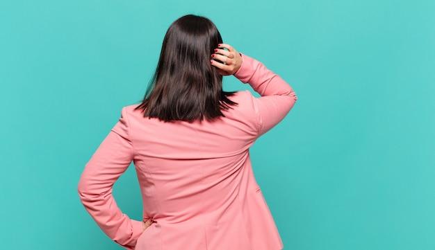 Jonge zakenvrouw die denkt of twijfelt, aan het hoofd krabt, zich verward en verward voelt, achter- of achteraanzicht