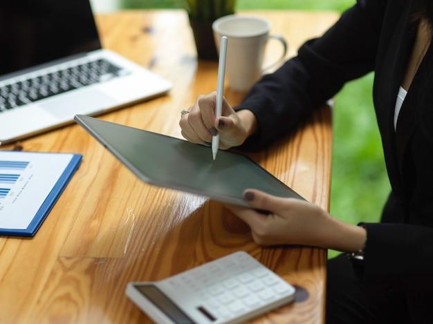 Jonge zakenvrouw die digitale tablet op kantoor gebruikt met styluspen zakenvrouw met tablet