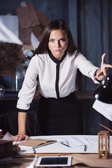 Jonge zakenvrouw die documenten naar de camera gooit. teleurgesteld en geïrriteerd door mislukt project.