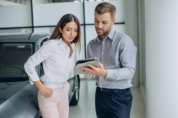 Jonge zakenvrouw die een auto koopt in de autoshowroom