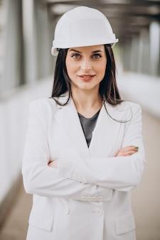 Jonge zakenvrouw die een helm draagt bij het bouwen van een object