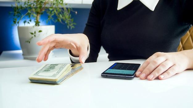Jonge zakenvrouw die een hoop geld vasthoudt met behulp van de rekenmachine op de smartphone.